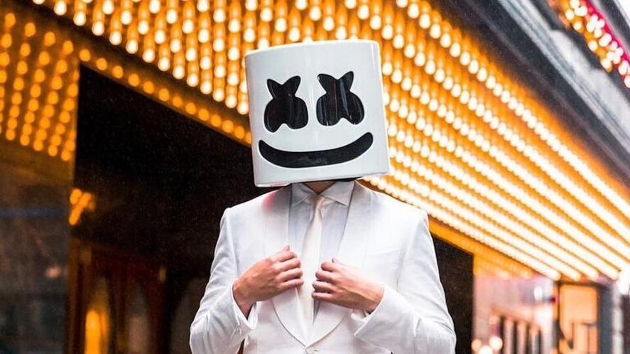 DJ Marshmello in a crisp white suit against lots of lights