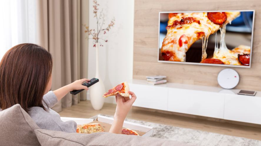 A woman eating a pizza while watching a TV show about pizza