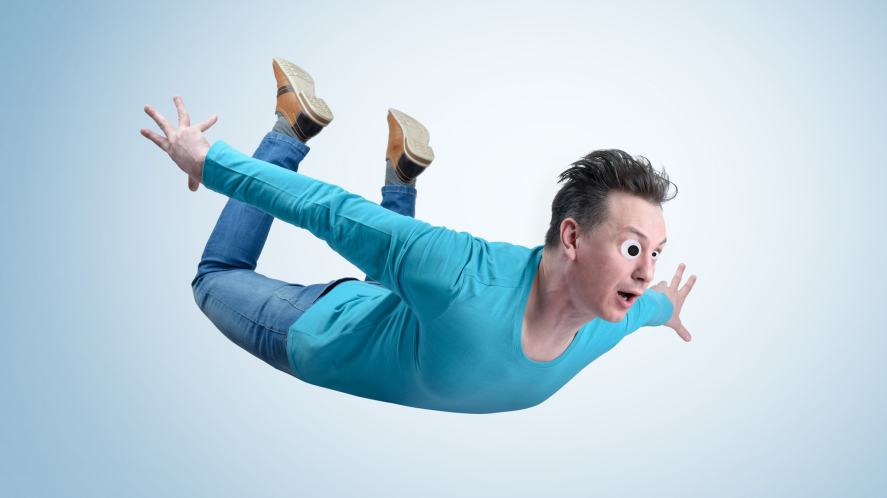 A man skydiving in a jumper and jeans