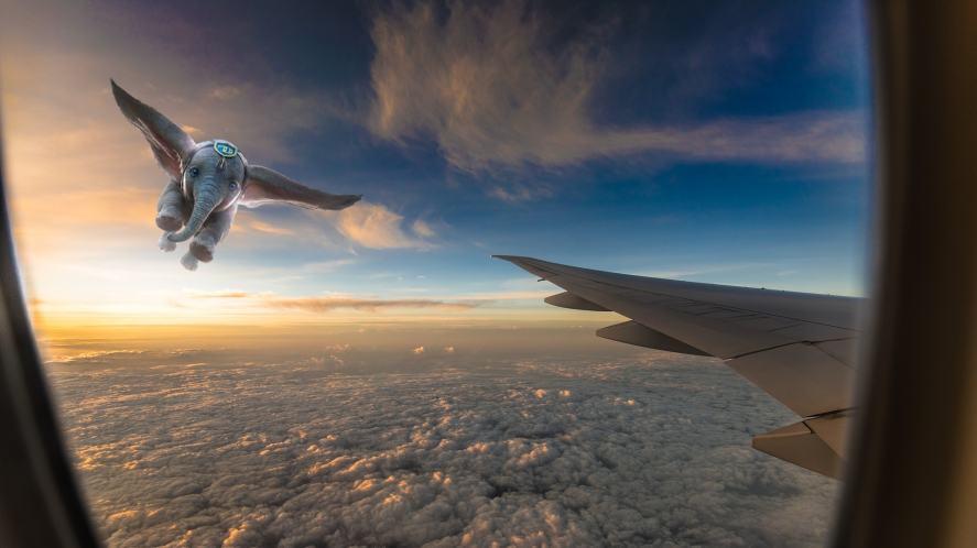 Dumbo flying next to an aeroplane