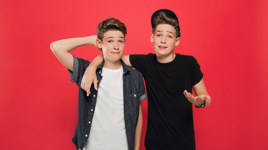 Max and Harvey pose against a red background