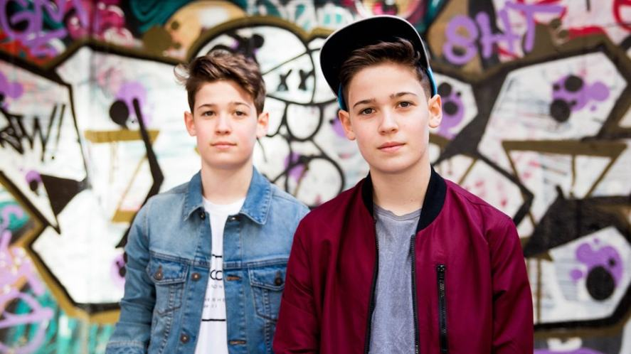 Max and Harvey stand in front of a graffiti wall