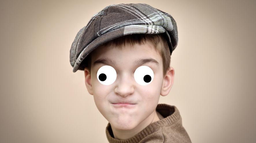 A boy in a cap pulling a face