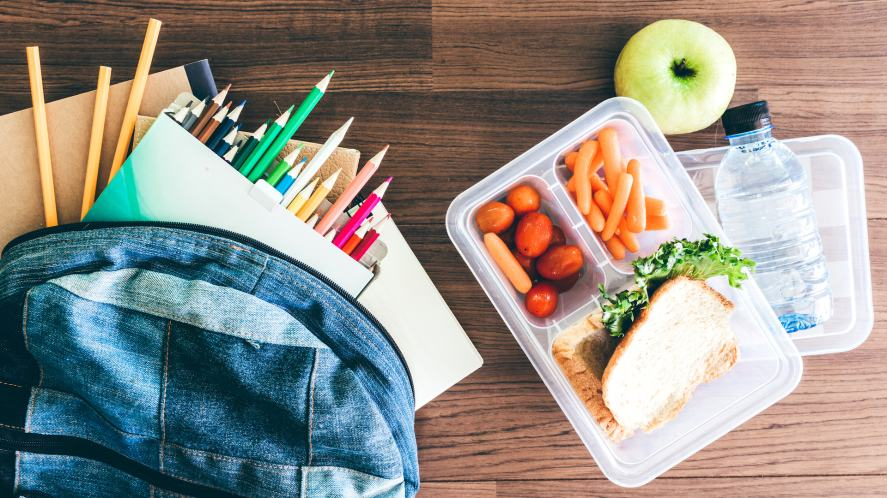 Lunch box with vegetables and slice of bread for a healthy school lunch on wooden table