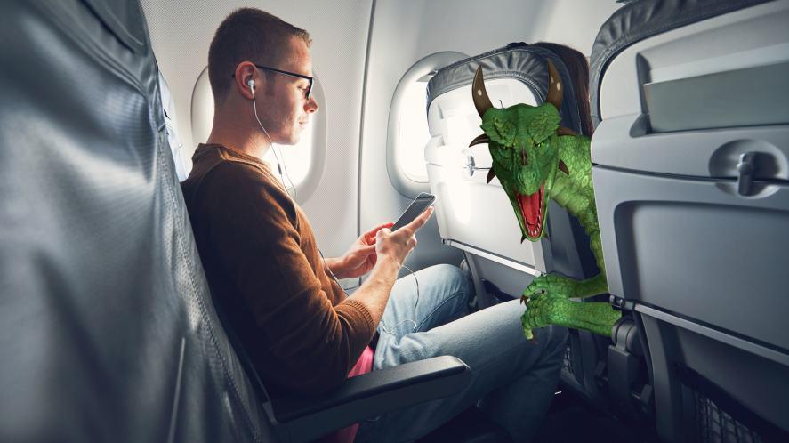 A dragon enjoying a flight on an aeroplane