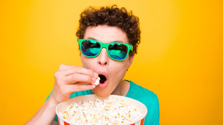 A person in sunglasses eating popcorn