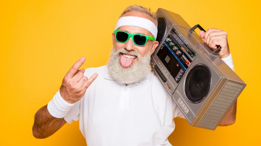 A bearded elderly teacher listening to music on an old portable stereo