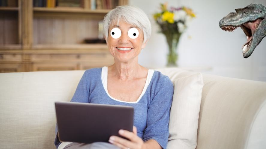 A gran reading a book on a tablet with a dinosaur in the background
