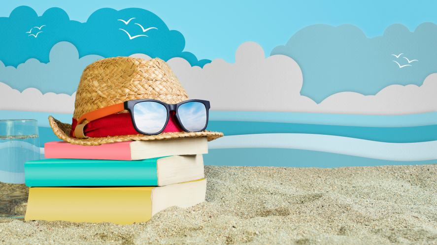 A pile of books on the beach... wearing a hat