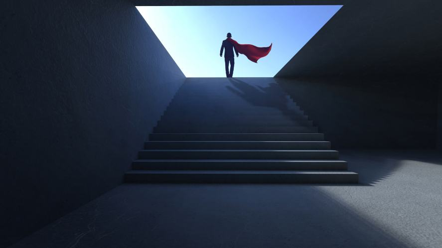 A man wearing a cape walking up stairs