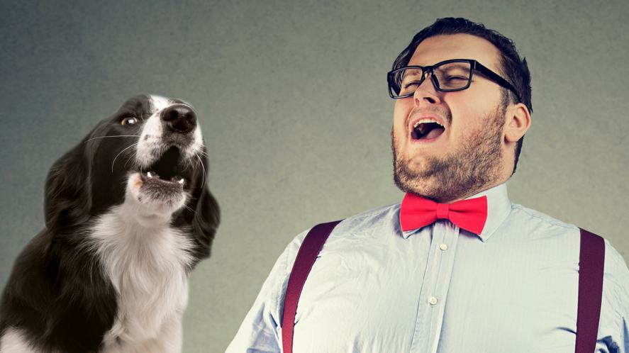 A man singing next to a howling dog