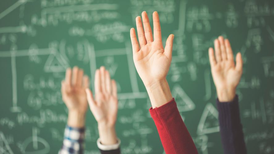 Students raising their hands in a maths lesson