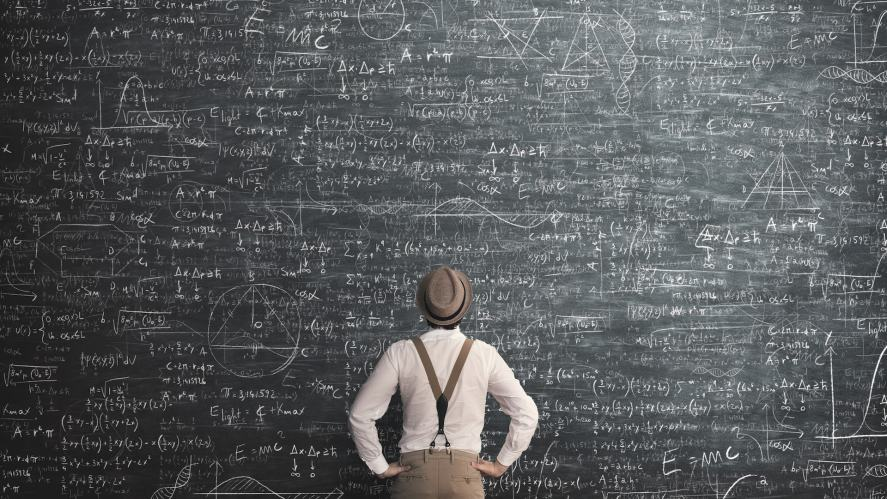 A person working out a problem on a huge chalkboard