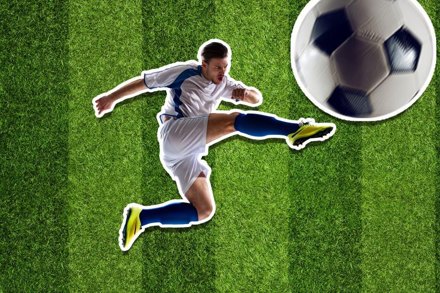 A footballer kicking a massive ball