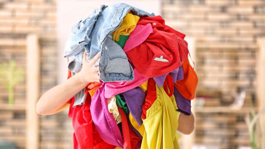 A person holding a pile of clothes