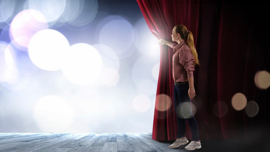 An actor on stage behind a red velvet curtain