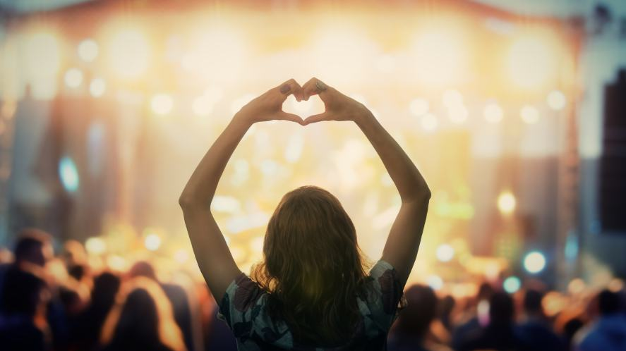 A person making a heart shape with their hands a pop concert
