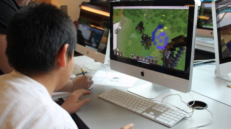 Someone playing Minecraft on a desktop computer