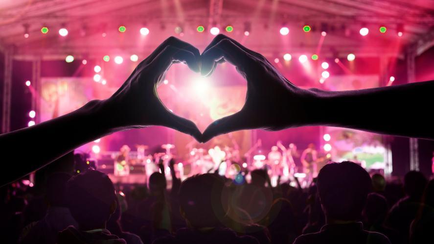 A pair of hands make a heart shape at a pop concert