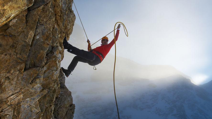 A rock climber on a very steep ledge