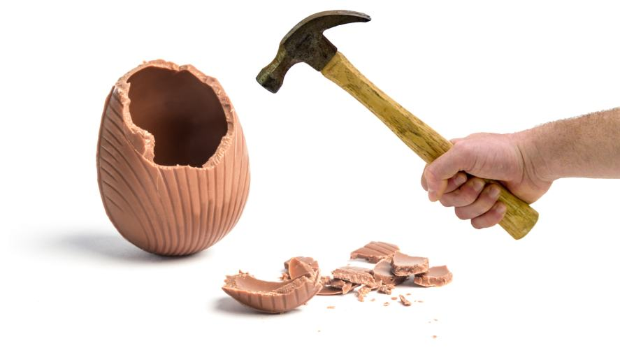 Easter egg being broken with a hammer