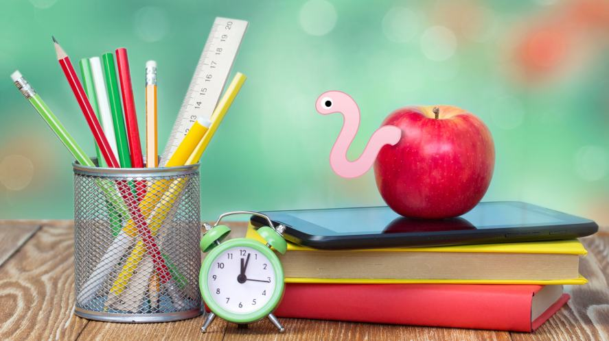 A worm poking out of an apple, next to a pile of homework