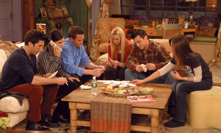 Friends cast all gathered around coffee table