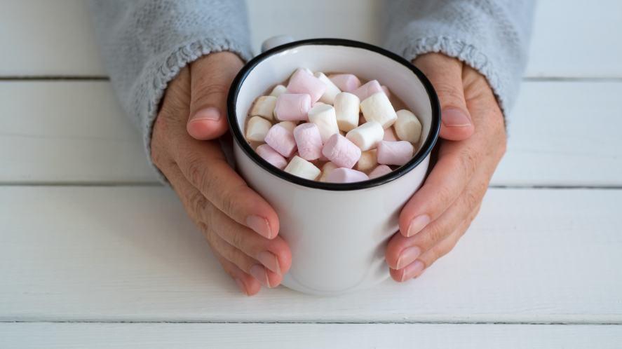 A pair of hands cradling a mug of hot chocolate