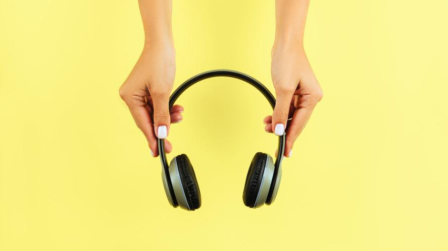 A pair of hands hold some wireless headphones