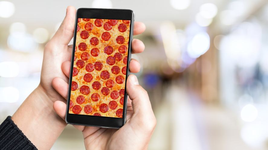 A person holding a mobile phone showing a slice of pizza