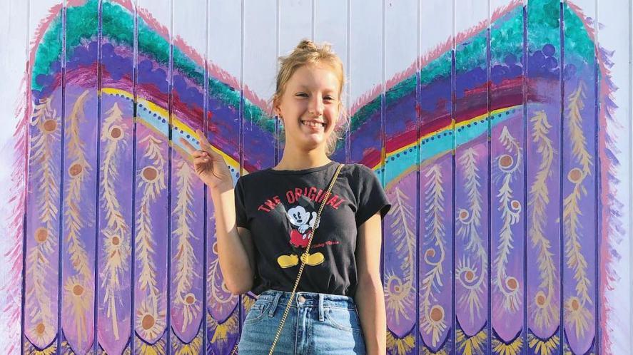 Karina poses next to some graffiti
