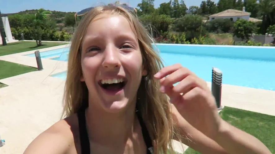 Karina next to an outdoor swimming pool