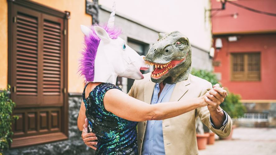 A couple dancing and wearing dinosaur t-rex and unicorn masks