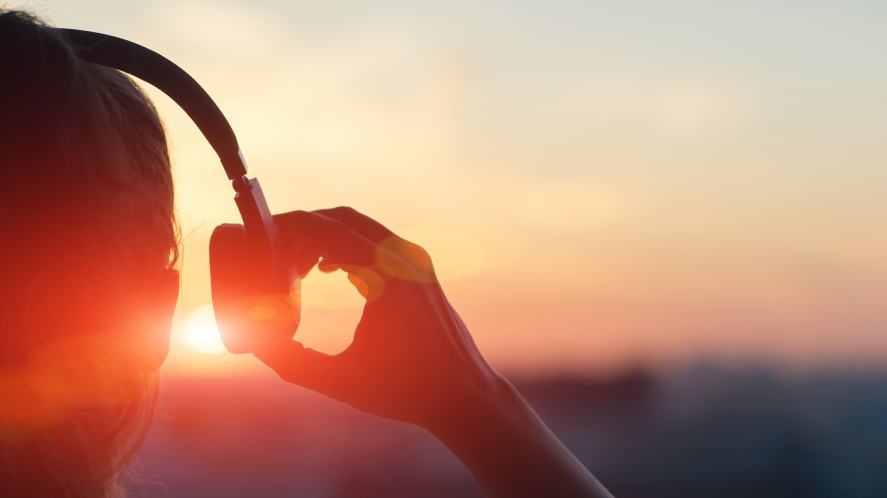 A person listening to music while the sun rises