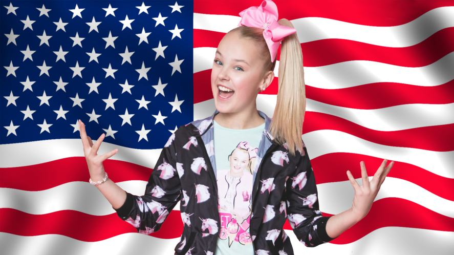JoJo standing in front of the American flag