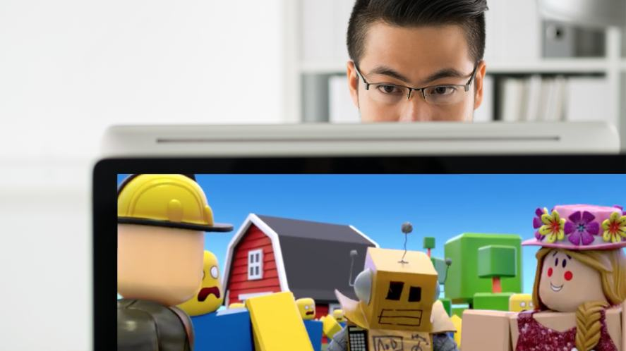 A man on a computer, with a Roblox game in the foreground