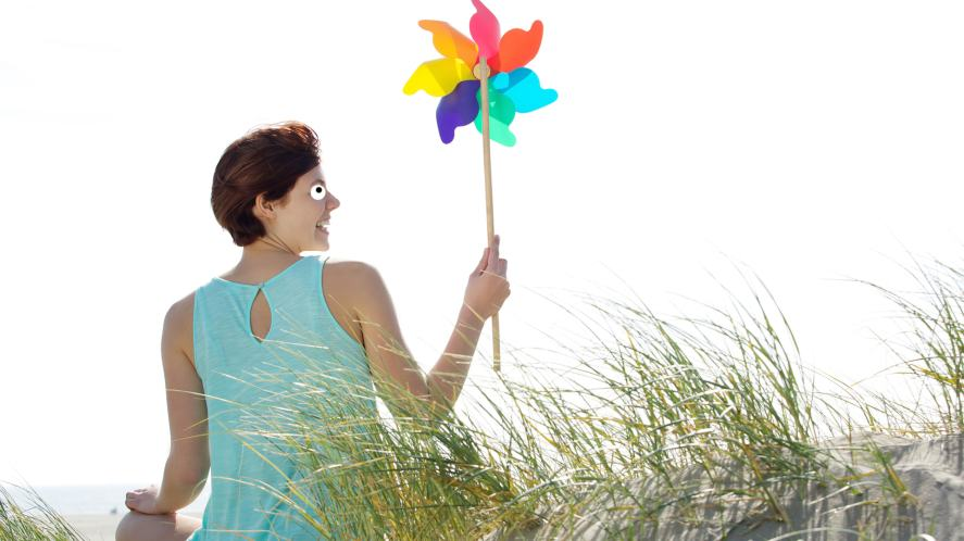 A woman sitting on a sand dune with a colourful pinwheel toy