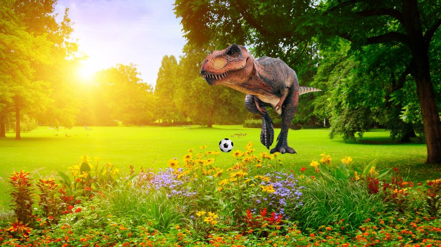 A dinosaur playing football in the park
