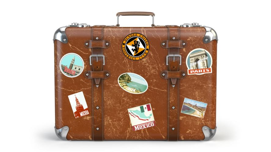 A suitcase covered in stickers from around the world