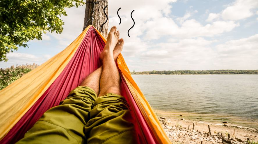 A man with stinky feet relaxing in a hammock by a lake
