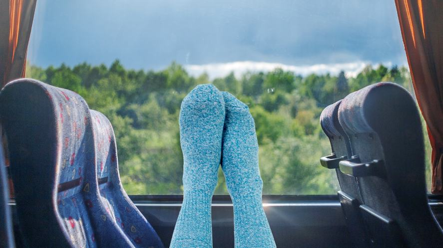 A pair of feet in socks relaxing on a bus
