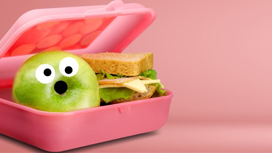 A packed lunch with a scared looking apple