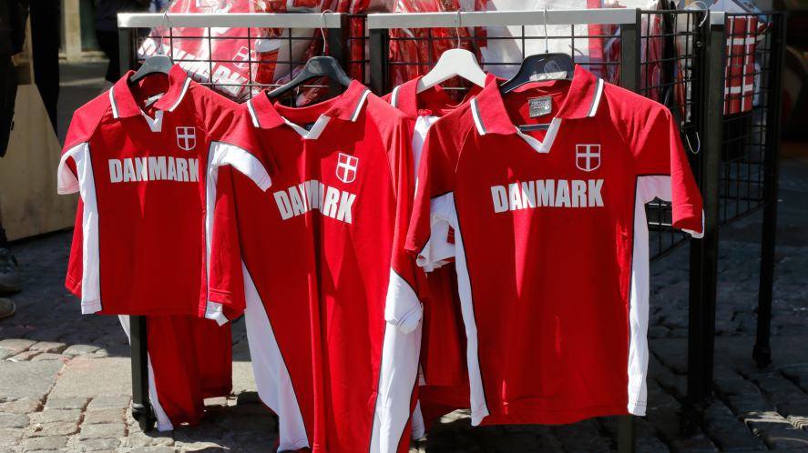 A selection of Denmark football shirts in a market