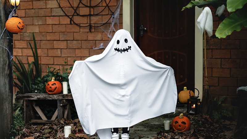 A white ghost in a garden surrounded by Halloween pumpkins