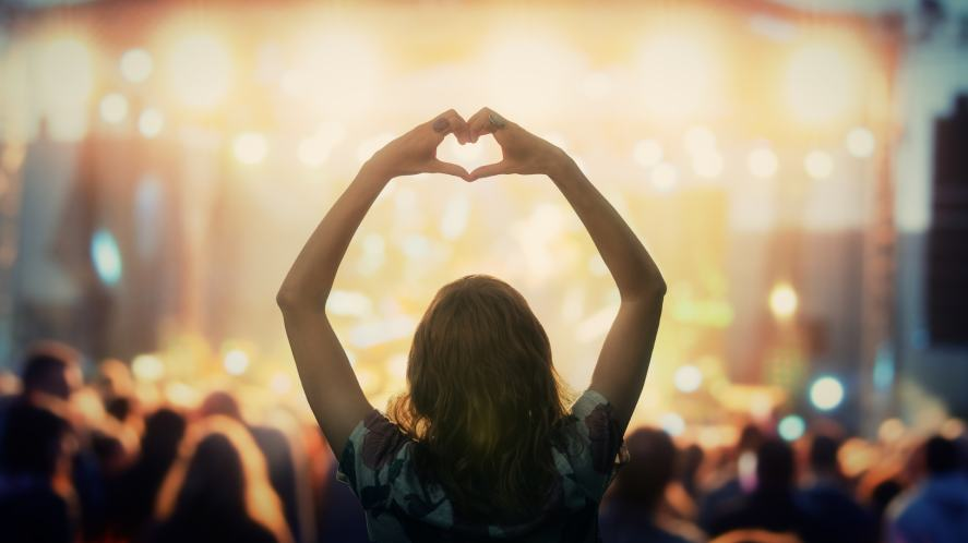 A person making a heart sign at an outdoor concert
