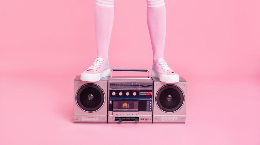 A person in pink socks standing on an old fashioned stereo