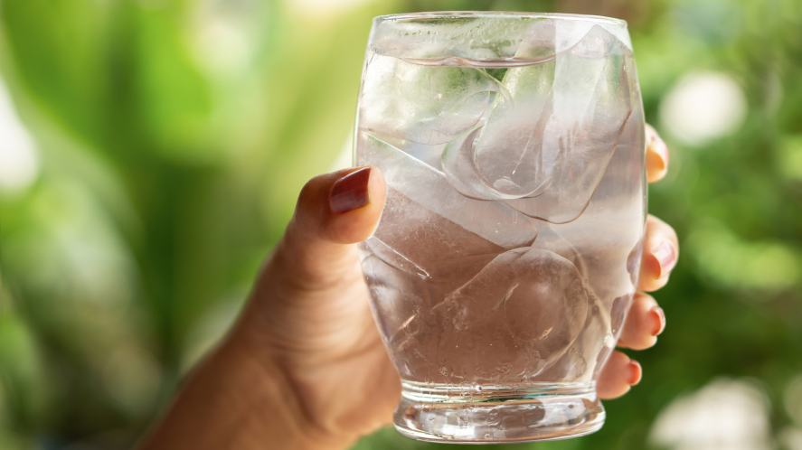 Woman hand holding glass of cold and fresh water with ice