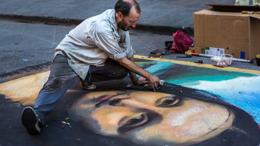 A street artist drawing on the pavement with chalk