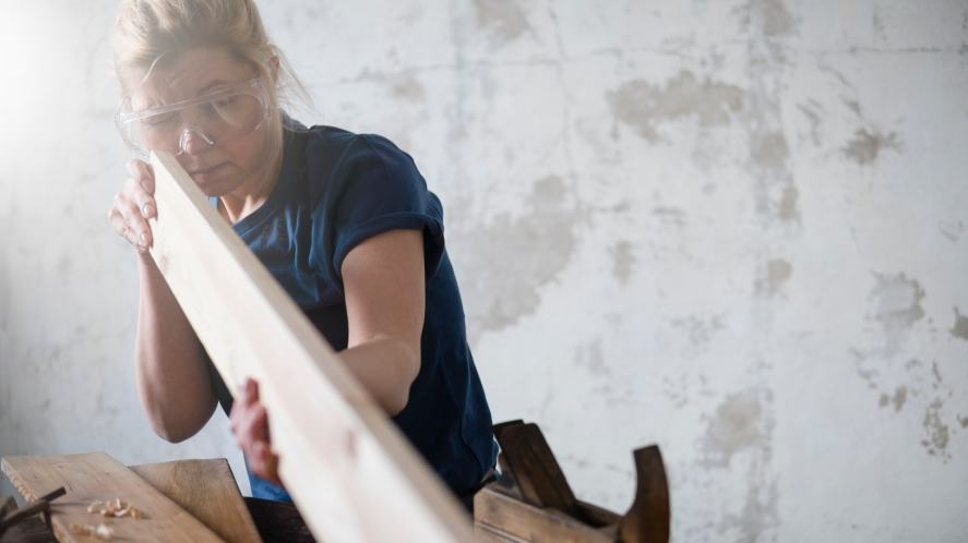 A carpenter checks a piece of wood, while wearing protective goggles