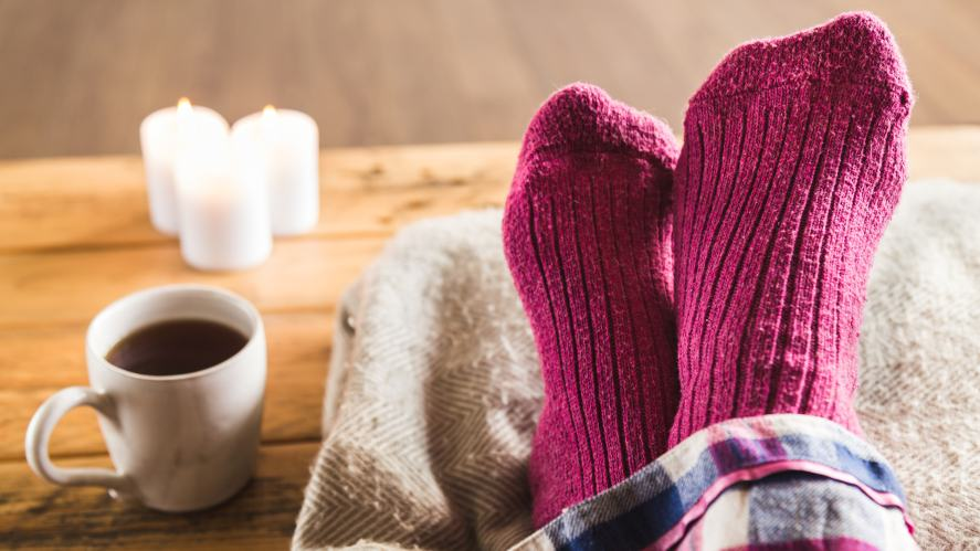 Feet in socks, relaxing with a hot drink